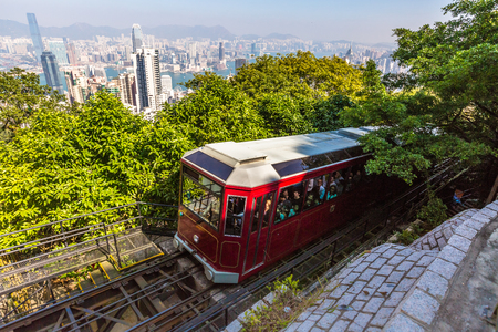 Hong Kong, China - December 10, 2016: The popular red Peak Tram to Victoria Peak, the highest peak of Hong Kong island. Tourist tram with panoramic city skyline in the background in a sunny day. Editorial