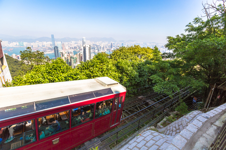 Hong Kong, China - December 10, 2016: The red Peak Tram to Victoria Peak, the highest peak of Hong Kong island. Tourist tram with panoramic city skyline in the background in a sunny day. Editorial