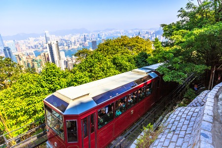 Hong Kong, China - December 10, 2016: The popular red Peak Tram as he arrives at the terminus of Victoria Peak, the highest peak of Hong Kong island, with panoramic city skyline background. Sunny day. Editorial