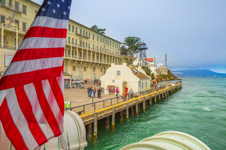 San Francisco, California, United States - August 14, 2016: Alcatraz penitentiary sally port with main building with guard tower. Dock full of tourists waiting for boat. American flag waving.