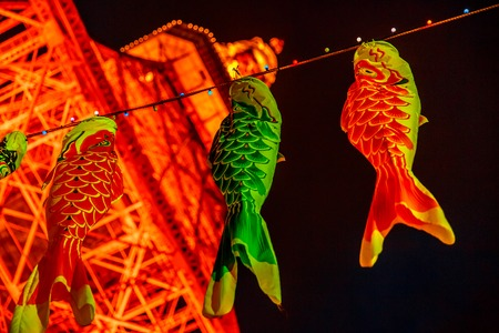 Tokyo, Japan - April 23, 2017: bottom view of Koinobori a carp-shaped wind socks traditionally flown in Japan to celebrate Childrens Day. Blurred Tokyo Tower by night on background. Night cityscape. Editorial