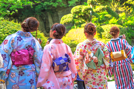 Kamakura, Japan - April 23, 2017: back of four Japanese ladies in zen garden, in traditional pink kimonos, admiring green zen garden in the nature of Takera Hokoku-ji Temple of Kamakura.