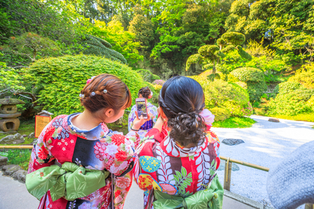Kamakura, Japan - April 23, 2017: Japanese women wearing Japanese traditional kimono take photo with smartphone at japanese zen garden inside Take-dera Temple in Kamakura. Editorial