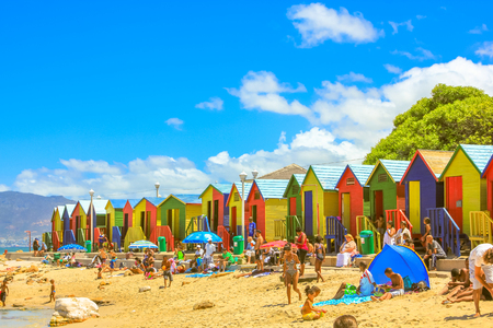 Cape Town, South Africa - January 10, 2014: many people on famous colorful beach cabins of white beach of Muizenberg in Cape Town city, Western Cape, South Africa. Blue sky in summer season.