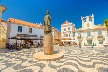 Cascais, Portugal - August 6, 2017: King Peter I Statues in Outubro Square, historic Cascais center, the most popular holiday destination on Lisbon coast.Typical Portuguese mosaic flooring. Blue sky. Editorial