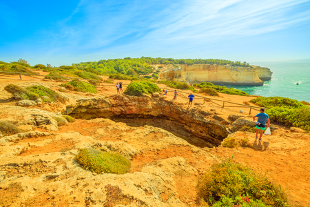 Benagil, Portugal - August 23, 2017: Benagil Cave seen from the top of rocky cliff in Algarve coast, Lagoa, Portugal. People watching the impressive sea caves from above. Summer holidays. Editorial