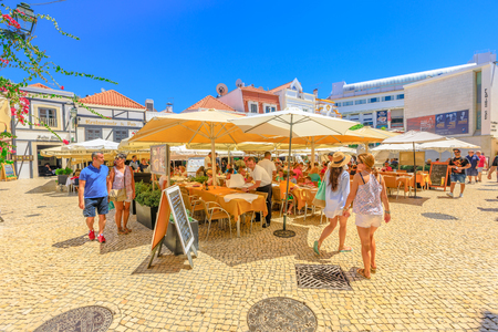 Cascais, Portugal - August 6, 2017: tourists walking through the historic center of Cascais and eating in restaurants and bars on Largo Luis de Camoes. People enjoying summer vacations.