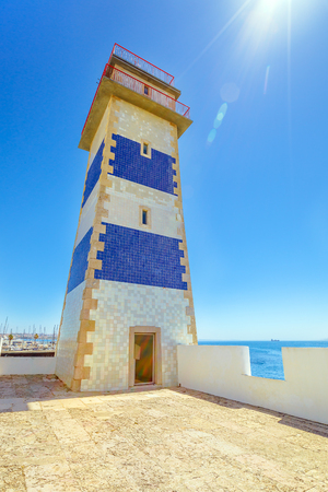 Perspective view of Santa Marta Lighthouse or Saint Marthas Lighthouse of Saint Mary in Cascais, Atlantic coast, Portugal. Sunny day in blue sky. Casais is a very popular tourist resort near Lisbon. Stock Photo