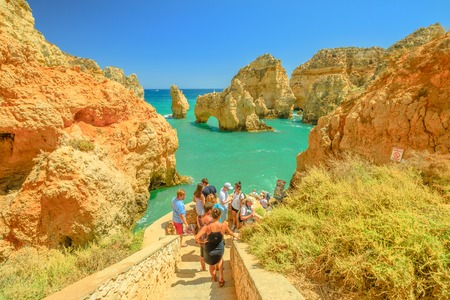 Lagos, Portugal - August 22, 2017: tourists on stairs awaiting boat trip for caves, arches and rock formations of Ponta da Piedade in Lagos, one of the main tourist destinations in the Algarve Coast. Editorial