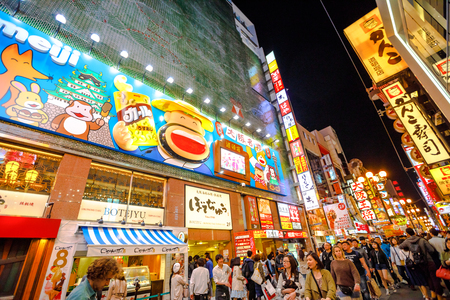 Osaka, Japan - April 29, 2017: crowd of tourists and Japanese people walking through the streets of Namba District by night with various food signages. The Golden Week are Japanese spring festivals.