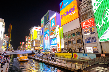 Osaka, Japan - April 29, 2017: night urban scene. Touristic boat in Dotonbori Canal and famous Glico Running Man sign in Dotonbori street, Namba, a popular shopping and entertainment district. Editorial
