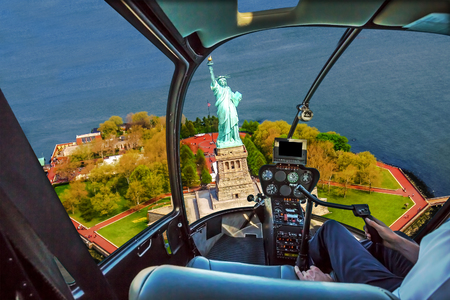 Helicopter cockpit with pilot arm and control console inside the cabin on Liberty Island and the famous Statue of Liberty monument symbol of New York City, United States.