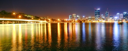 Panorama of Narrows Bridge and Perth Skyline illuminated at night. Perth Downtown cityscape with skyscrapers reflecting on the Swan River from Mill point, Western Australia.