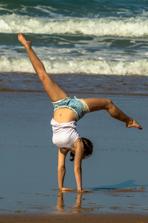 Cape Town, South Africa - August 30, 2014: Gymnast woman practices yoga on the beach. A young altleta practicing for a competition