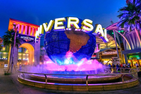 Singapore - May 2, 2018: Universal Studios with luminous globe in Sentosa island at blue hour with pink lights. Universal Studios Singapore is southeast Asias first Hollywood movie theme park.