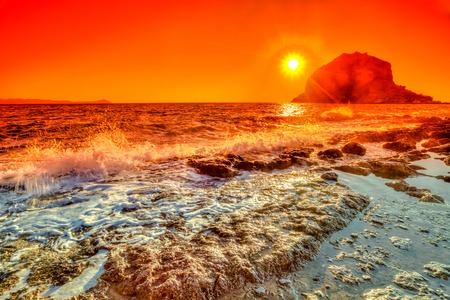 Spectacular colorful sunrise on the beach in front of a castle in Monemvasia, Lakonia, Peloponnese, Greece.