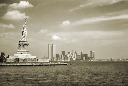 Statue of Liberty and Twin Towers, destroyed in September 11, 2001, of World Trade Center. New York City skyline view from the ferry. Sepia background, vintage style.