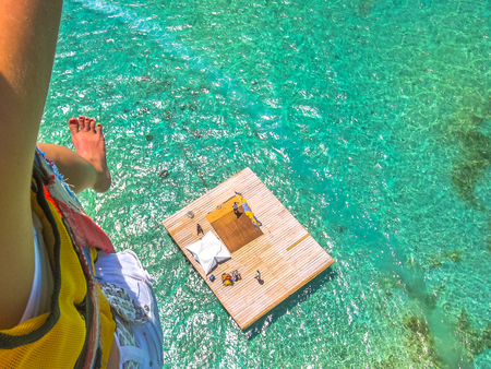 Aerial closeup view of a woman parasailing. Below, the landing platform on the spectacular blue sea of Deer Island, east coast of Mauritius, Indian Ocean.