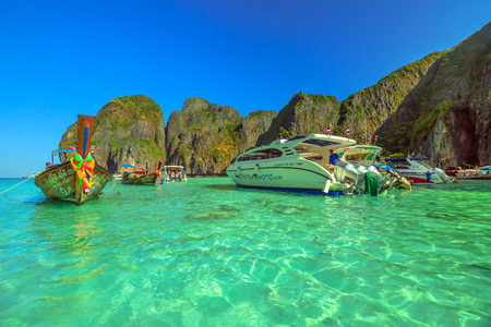 Maya Bay, Phi Phi Leh, Thailand - December 31, 2015: longtail boat and big motorboat parking in Maya Bay lagoon. Mass tourism has damaged and polluted the heavenly island of Ko Phi Phi Leh.