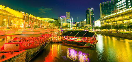Scenic Clarke Quay Riverside area with cruise docked at pier in Singapore, Southeast Asia at dusk. Waterfront skyline reflected on Singapore River. Popular attraction for nightlife. Stock Photo