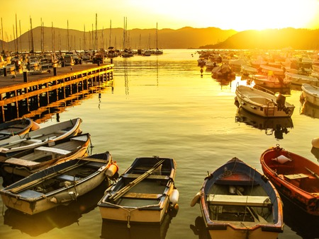 Gulf of Poets with sailing and motorboats at sunset light in Lerici medieval town in La Spezia province, Ligurian Coast, Italy. Scenic Lerici Port with wooden jetty.