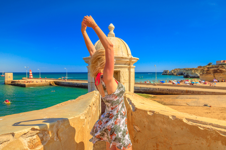 Tourism in Portugal. Freedom lifestyle female tourist on top of Fort of Ponta da Bandeira, Lagos, Portugal. Caucasian woman enjoying at Lagos, historic city on Algarve coast. Holidays in Europe.
