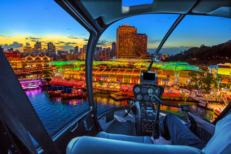 Helicopter cockpit interior flying on aerial skyline of Clarke Quay and riverside area at sunset in Singapore, Southeast Asia. Waterfront skyline on Singapore River. Popular nightlife attraction.