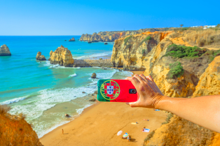 Tourism and travel concept in Algarve. Mobile phone with Portugal flag cover taking photos of Praia do Pinhao in Lagos on Algarve coast, Portugal, Europe. In the distance the famous Dona Ana Beach
