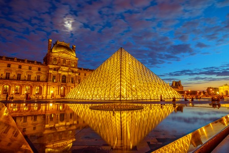 Paris, France - July 1, 2017: twilight reflections around Louvre Museum glass pyramid. Louvre palace in the courtyard. Picture gallery landmark hosting Mona Lisa painting by Leonardo Da Vinci. Editorial