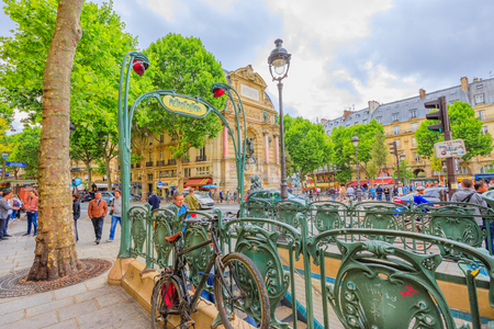 Paris, France - July 1, 2017: Entrance to subway with Fontaine Saint-Michel on background. The sign of the underground in Paris in classical liberty style in Place Saint-Michel.