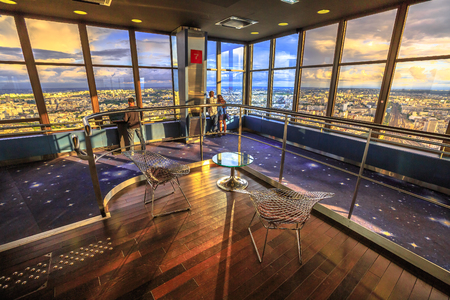 Paris, France - June 30, 2017: romantic couple looking at panoramic views of Paris at sunset inside Montparnasse Observation Deck. Montparnasse skyscraper is the highest observation point in the city.