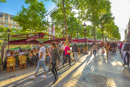 Paris, France - July 2, 2017: tourists walk on the most famous avenue of Paris, the Champs Elysees, for shopping in luxury shops. Lifestyle people sitting at Cafe George V. Sajtókép