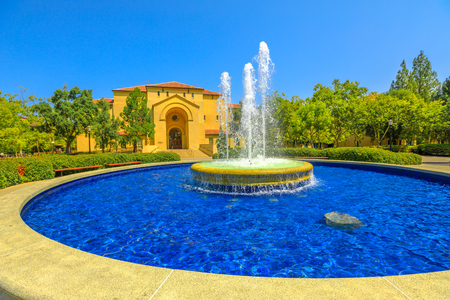 Palo Alto, CA, United States - August 13, 2018: Fountain and Memorial Auditorium on background. Stanford University is one of the worlds leading teaching and research institutions.
