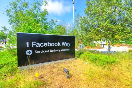 Menlo Park, California, United States - August 13, 2018: Facebook HQ entrance sign on new campus in Silicon Valley. On background a young employee goes to work with the company bicycle. Éditoriale