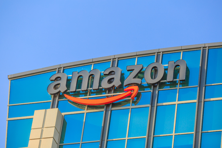 Sunnyvale, California, USA - August 13, 2018: closeup of Amazon Sign atop of glass building of Big Amazon campus in Silicon Valley. Amazon is leader in electronic commerce and cloud computing. Редакционное