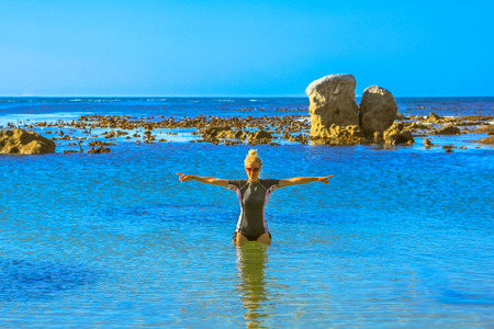 South Africa summer holidays. Blonde woman with snorkeling clothing enjoying in Sea Point, one of the suburbs of Cape Town. Female tourist with Atlantic Ocean on background. Blue sky, copy space.