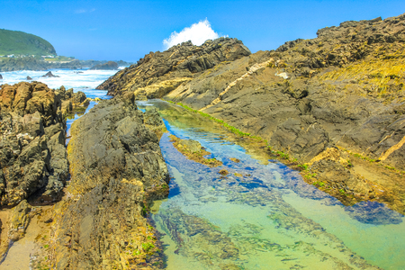 Rocks, tide pools and crashing waves in Tsitsikamma Nature Reserve on Garden Route in South Africa. The natural pools of the Storms River are a popular attraction in the Eastern Cape.Blu sky in summer Stock Photo