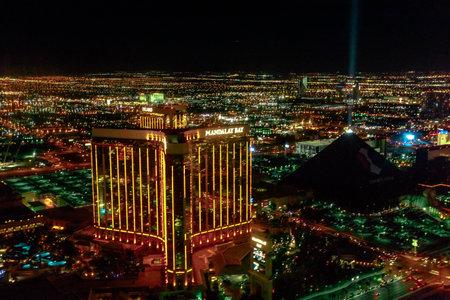 Las Vegas, Nevada, United States - August 18, 2018: aerial view of Las Vegas Skyline by night. Scenic flight above Luxor pyramid Hotel Casino with light show and Mandalay Bay Resort Casino.