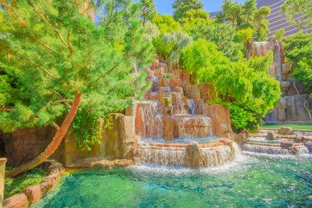 Las Vegas, Nevada, United States - August 18, 2018: closeup of Wynn Las Vegas Waterfall Fountain in the garden outdoors in blue sky day. The Wynn is Resort Hotel 5-star casino, Las Vegas Strip. 報道画像