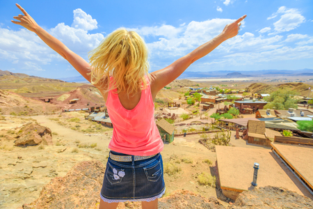 Woman with open arms enjoying at aerial view of Calico atop of overlook. Calico is a Ghost Town and former Mining town in Calico Mountains of Mojave Desert region of California, United States.