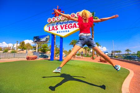 Young woman jumping at Welcome to Fabulous Las Vegas Nevada Sign, popular landmark on Las Vegas Strip at entrance of the city. Happy tourist traveler in Nevada, Unites States. Blue sky.