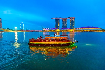 Singapore - April 28, 2018: Skyline of Singapore with cruise sails in the harbor at blue hour. Tourist boat on foreground. Night scene waterfront in marina bay area. Editöryel