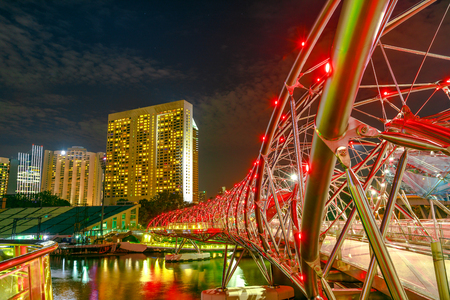 Singapore - April 26, 2018: Architecture of pedestrian bridge illuminated at night in the foreground in Marina Bay Area, Singapore city. Famous place for travel destination.