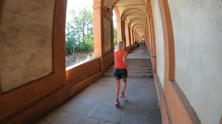 A sporty woman running under San Lucas portico: the longest porch in the world leading to the San Luca Sanctuary on Colle della Guardia. Bologna city of Italy.