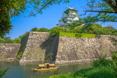 Osaka, Japan - April 30, 2017: touristic boat with tourists along the moat of Osaka Castle one of the best activities you can experience around Osaka Castle area, one of most famous landmarks of Japan
