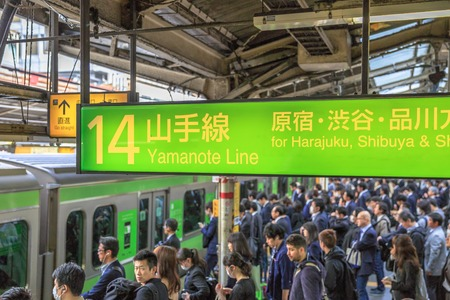 Tokyo, Japan - April 17, 2017: green Yamanote Line signboard for Harajuku, the most important train line in Tokyo. Crowd of commuters waiting for rail train at Tokyo main railway station 報道画像