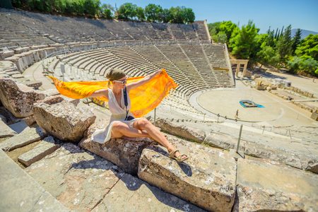 Smiling woman with orange sarong and greek clothes enjoying Ancient Theatre Epidaurus amphitheater in Peloponnese, Greece. European travel destination. Historical heritage and landmarks.