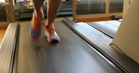 Running shoes training. Woman feet in colorful shoes running on treadmill machine indoor. Fitness center training. Healthy lifestyle concept.