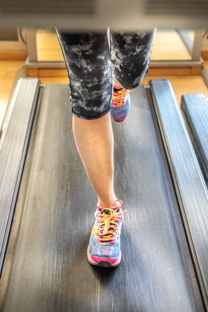 woman feet in colorful shoes running on treadmill machine indoor. Fitness center training. Healthy lifestyle concept. Archivio Fotografico