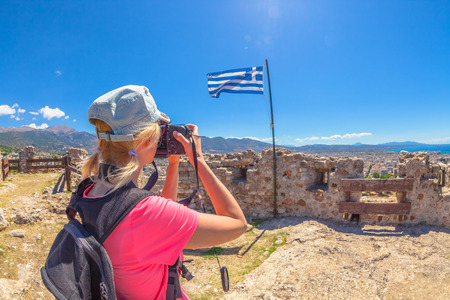 Traveler woman photographer with professional camera takes shot of Patra Castle ruins, Peloponnese, Greece. Caucasian female photographing outdoors. Europe travel concet. Flag of Greece on background.